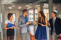 Vier bedrijfsmensen die in bureauhal spreken stock foto
