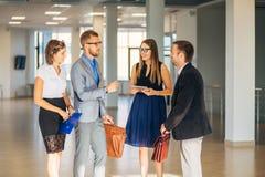 Vier bedrijfsmensen die in bureauhal spreken royalty-vrije stock afbeelding