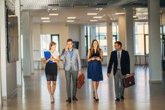 Vier bedrijfsmensen die en in bureauhal spreken lopen royalty-vrije stock foto