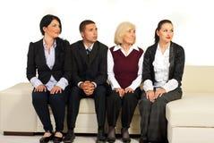Vier bedrijfsmensen die op bank weg kijken Stock Fotografie
