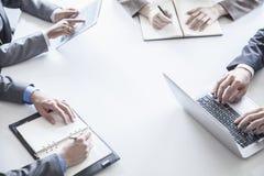 Vier bedrijfsmensen rond een lijst en tijdens een commerciële vergadering, slechts handen Stock Afbeelding