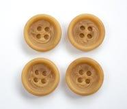 Vier beige Plastikknöpfe lokalisiert auf Weiß Stockfotografie