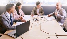 Vier Berufsführungskräfte, die ein Geschäftstreffen des frühen Morgens leiten stockfotos