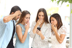 Vier besorgte Freunde, die intelligentes Telefon aufpassen Stockfoto