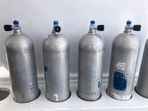 Vier bevindt groot metaal zich, de flessen van de aluminiumzuurstof voor ademhaling, die met kleppen, versnellingsbakken duiken o stock foto