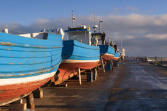Vier Blauwe vissersboten in droogdok wachtende reparatie stock foto's