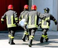 Vier brandweerlieden in actie dragen een brancard stock fotografie