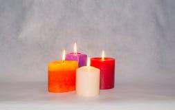 Vier brennende farbige Kerzen Stockbilder