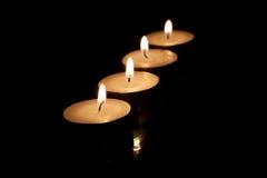 Vier brennende Kerzen auf einem schwarzen Hintergrund Stockbilder
