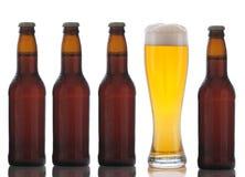 Vier Brown-Bierflaschen und volles Glas lizenzfreies stockfoto