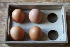 Vier bruine eieren in een houten doos met ruimte voor zes eieren, in wind Royalty-vrije Stock Fotografie