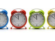 Vier bunte Alarmuhren getrennt auf weißem Hintergrund 3D Lizenzfreie Stockbilder
