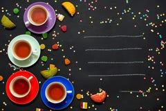 Vier bunte Tassen Tee, Marmelade und Kekse auf einem schwarzen Hintergrund Freier Platz für Text Lizenzfreies Stockfoto