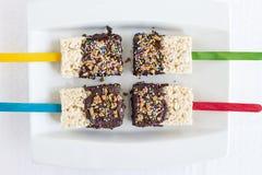Vier cakes van Rijstkrispie die in chocolade worden ondergedompeld stock fotografie