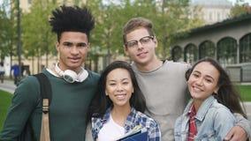 Vier charmante glimlachende vrienden bevindt zich vóór camera op langzame wijze stock videobeelden