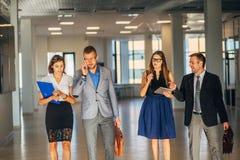 Vier collega's gaan rond het bureau en communiceren royalty-vrije stock foto
