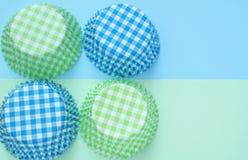 Vier cupcakevormen van document in groene en blauwe die kleuren, in een vierkant worden geschikt stock foto's