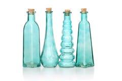 Vier cyaan gekleurde glasflessen verschillende vormen Royalty-vrije Stock Fotografie