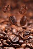 Vier dalende bonen en donkere geroosterde koffie Stock Foto's