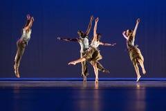 Vier dansers stellen tegen donkere achtergrond op stadium Stock Afbeeldingen