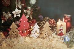 Vier dekorative hölzerne Weihnachtsbäume mit geschnitzten Buchstaben Weihnachten und Weihnachtsverzierungen stockbild