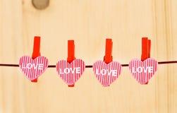 Vier dekorative Herzen, die am hölzernen Hintergrund, Konzept des Valentinstags in der Liebe hängen Lizenzfreie Stockfotografie