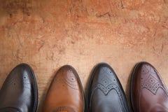 Vier dichte omhooggaand van de mensenschoen op een achtergrond van uitstekende muur Stock Fotografie