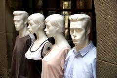 Vier die ledenpoppen op de buitenvenstervensterbank worden getoond van kleden zich Stock Foto's