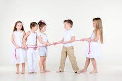 Vier diskutierende kleine Mädchen und Junge zeichnen über Seil Stockbild