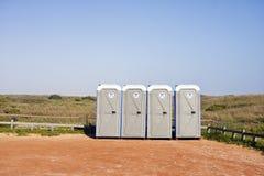 Vier draagbare toiletten in grintparkeerterrein Royalty-vrije Stock Afbeelding