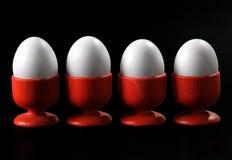 Vier eieren in rode koppen op zwarte achtergrond Royalty-vrije Stock Afbeeldingen