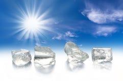 Vier Eiswürfel, Sonne und blauer Himmel Stockbild