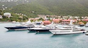 Vier enorme Yachten in der Bucht Stockfotos