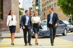 Vier erfolgreiche Geschäftsleute, welche die Straße in der Stadt kreuzen Lizenzfreie Stockfotos