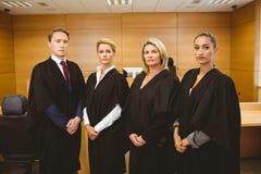 Vier ernstige rechters die terwijl het dragen van robes bevinden zich stock afbeelding