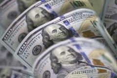 Vier etwas gebogenes hundert US-Dollar Banknoten auf hundert US-Dollar berechnet Hintergrund Stockfotografie