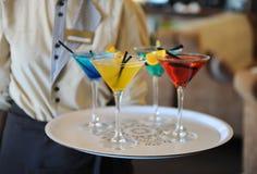 Vier färbten Cocktails auf einem Behälter in den Händen des Kellners Gelb, blau, grün, rot Verziert mit einer Zitronenscheibe Stockfotos