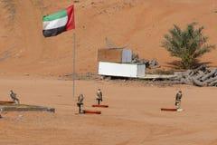 Vier Falken stehen an ihrem Ausbildungsposten mit einer UAE-Flagge im Hintergrund stockfotos