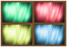 Vier farbige Gläser im Holzrahmen Stockfotografie