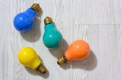 Vier farbige Glühlampen auf einem hölzernen Hintergrund Lizenzfreie Stockbilder