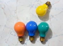 Vier farbige Glühlampen auf einem Marmorhintergrund Lizenzfreie Stockfotos