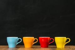 Vier farbige Kaffeetassen auf dem Weinleseholz Lizenzfreies Stockfoto
