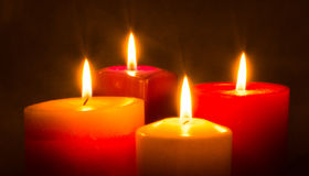 Vier farbige Kerzen, die in der Dunkelheit brennen Stockfoto