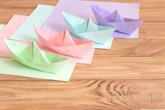 Vier farbige Origamibootsspielwaren auf einem Holztisch Quadratische Blätter des farbigen Papiers Kreative Papierhandwerksidee fü Stockfotografie