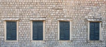 Vier Fenster in der alten Wand mit geschlossenen blauen Fensterläden stockfotos