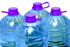 Vier flessen water dat over wit wordt geïsoleerd Stock Foto's
