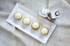 Vier Franse Vanille Cupcakes en melk in flessenglas Stock Foto