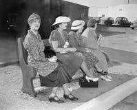 Vier Frauen, die auf einer Bank wartet auf den Bus sitzen (alle dargestellten Personen sind nicht längeres lebendes und kein Zust lizenzfreie stockfotografie