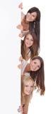 Vier Frauen, die an einem leeren Zeichen blicken Stockfoto