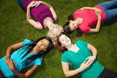 Vier Frauen, die in einem Park ein Sonnenbad nehmen Stockfotos